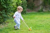 Beautful Curly Baby Girl Playing In The Garden With A Wooden Toy