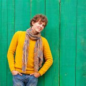 Smiling Curly Man In Yellow Sweater And Scarf On Green Wooden Background