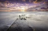 Lonely Destroyed Pier Extending Deep Into The Ocean At Sunset