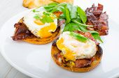 stock photo of benediction  - Eggs benedict with bacon and spinach on white plate - JPG