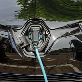 Charging Modern Electric Car With Power Supply Plugged In