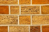 Yellow And Orange Shell Limestone Brick Wall As Abstract Background.