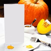 Autumn Thanksgiving Dinner Table Setting With Pumpkins And Blank Greeting Card Over Wooden Backgroun