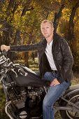 Man In Black Jacket Motorcycle One Hand On Handlebars Looking Trees