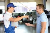 pic of garage  - Mechanic giving car key while shaking hand to a client in a garage - JPG