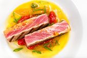 Grilled Tuna Steak With Sauce, Herbs And Cherry Tomatoes In A White Plate Served For Dinner. Studio