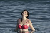 Girl Lifting Her Face To The Sun Standing Waist-deep In Water.