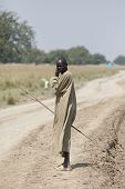 JONGLEI, SOUTH SUDAN-DECEMBER 4, 2010: Unidentified shepherd walks down the road in Jonglei county, South Sudan