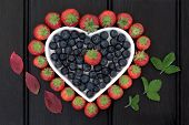 Blueberry and strawberry antioxidant fruit in a heart shaped dish with corresponding leaf sprigs.
