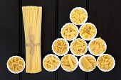 Spaghetti pasta dried food selection in a bundle and in porcelain crinkle bowls  over dark wood  background.