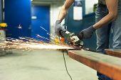 Man Hands Sawing Metal With Sparks In Workshop. Metalworking.