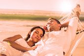 Peaceful couple napping in a hammock at the beach