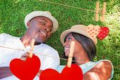 Happy couple lying in garden together on the grass against hearts hanging on the line