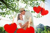 Cute couple standing in the park embracing against hearts hanging on a line