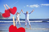 stock photo of barefoot  - Happy couple jumping up barefoot on the beach against hearts hanging on a line - JPG