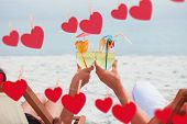 Couple clinking glasses of cocktail on beach against hearts hanging on a line