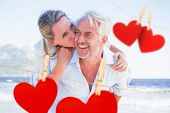 Man giving his smiling wife a piggy back at the beach against hearts hanging on a line
