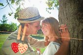 Cute smiling couple leaning against tree in the park against hearts hanging on the line