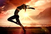Side view of a sporty young woman stretching against sunrise over magical sea