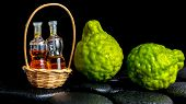 Aromatic Spa Concept Of Bergamot Fruits And  Bottles Essential Oil In Basket On Zen Basalt Black Sto