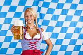 Young happy woman in dirndl holding Oktoberfest beer stein (Mass).