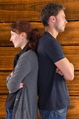 Irritated couple ignoring each other against overhead of wooden planks