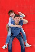 Man giving girl a piggy back against red wooden planks