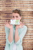 Pretty woman showing an one hundred euro note against wooden planks