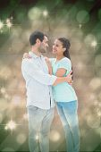 Attractive young couple hugging each other against light design shimmering on green