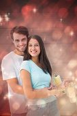 Happy young couple painting together against light design shimmering on red