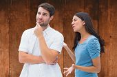 Angry brunette shouting at boyfriend against weathered oak floor boards background