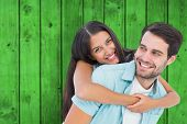 Happy casual man giving pretty girlfriend piggy back against bright green wooden planks