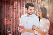 Attractive young couple holding a model house against light design shimmering on red