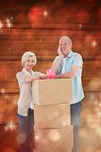 Older couple smiling at camera with moving boxes and piggy bank against light design shimmering on red