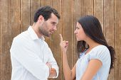 Angry couple facing off during argument against wooden planks