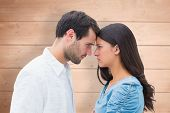 Angry couple staring at each other against overhead of wooden planks