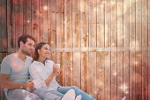 Cute couple sitting having coffee against light design shimmering on red