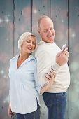 Happy mature couple looking at smartphone together against light design shimmering on red