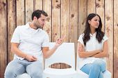 Man pleading with angry girlfriend against wooden planks