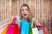 Overwhelmed young woman with shopping bags against wooden planks