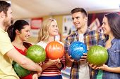people, leisure, sport, friendship and entertainment concept - happy friends holding balls and talking in bowling club