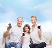 family, technology, advertisement and people concept- smiling mother, father and little girl with smartphones over blue sky background
