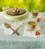 Easter Table With Tea Matcha Cheesecake And White Coffee On Background Of Green Grass