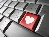 foto of lovers  - Online love and valentines lovers concept with a heart icon and symbol on a red computer key - JPG