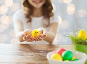 easter, holiday and child concept - close up of girl holding pot with green grass, yellow chicken toy and bowl of colored eggs on table over lights background