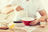 cooking and home concept - close up of male hand pouring milk in bowl