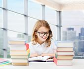 education, people, children and school concept - happy student girl in eyeglasses reading book at school over classroom background