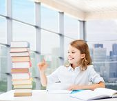 education, people, children and school concept - happy student girl sitting at table and counting books over classroom background