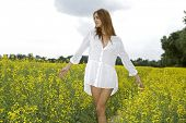 Portrait of beautiful attractive and sensuality sexy pretty brunette woman in white shirt on a yellow flowers field and blue sky