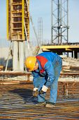 stock photo of concrete pouring  - builder worker knitting metal rebars into framework reinforcement for concrete pouring at construction site - JPG